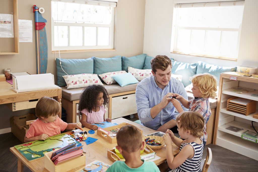 Daycare director and children working at table on shapes